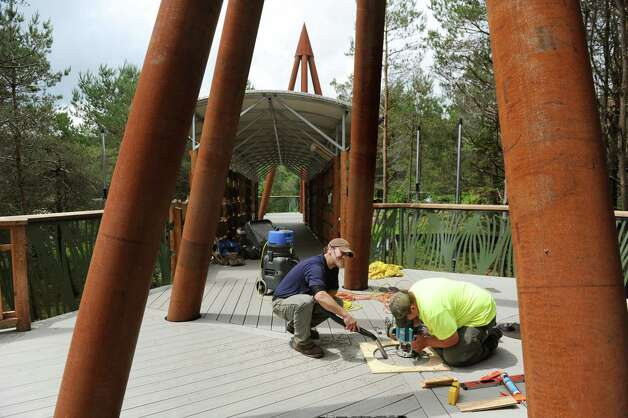 Brian Johnson, center, and Kody Largett, both of Northland Assoc., work to install honorary plaques on new Wild Walk on Tuesday, June 23, 2015, at the Wild Center in Tupper Lake, N.Y. (Cindy Schultz / Times Union) Photo: Cindy Schultz / 00032307A