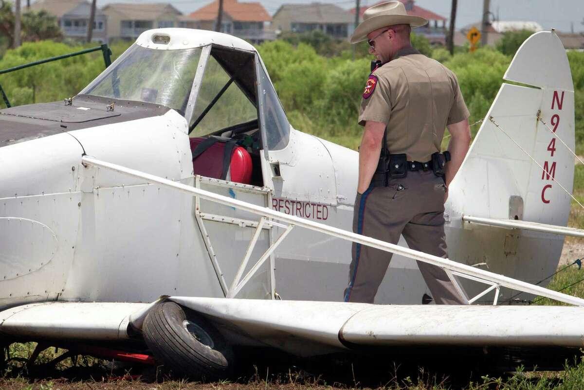 DPS trooper Corey Bean looks into the cockpit of a single seater plane that crash landed in a pasture off in Galveston, Texas on Saturday, June 27, 2015. (Stuart Villanueva/The Galveston County Daily News via AP)