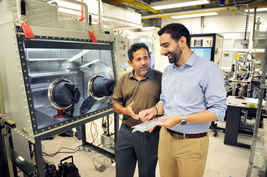 SUNY Poly VP Pradeep Haldar, left, and BESS Tech's Fernando Gomez-Baquero discuss battery technology in a SUNY Poly campus lab at CNSE Tuesday June 23, 2015 in Albany, NY. (John Carl D'Annibale / Times Union)