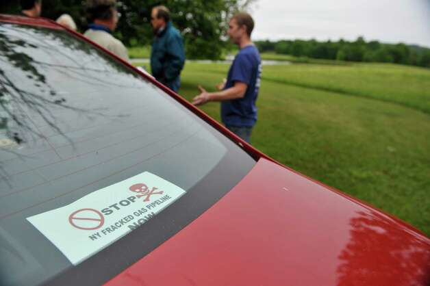 A bumper sticker is seen in the back window of a car as some residents talk with each other on Thursday, June 3, 2015, in Nassau, N.Y.  This group of residents are against a proposed Northeast Energy Direct gas pipeline that would run through this area.    (Paul Buckowski / Times Union) Photo: PAUL BUCKOWSKI / 00032087A