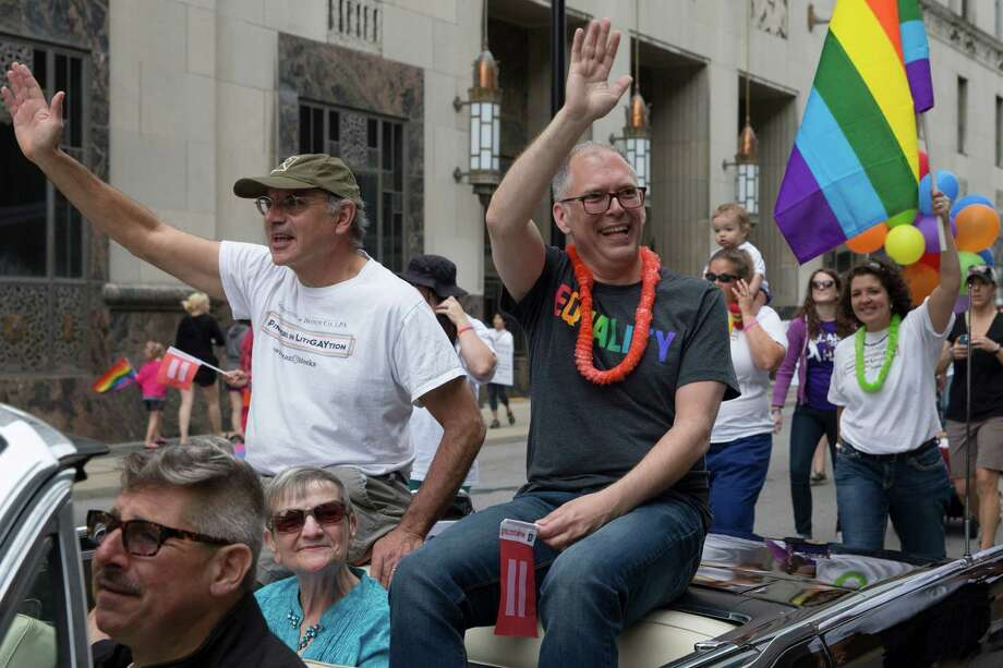 Gay marriage plaintiff Jim Obergefell, center, waves during the Cincinnati Pride parade, Saturday, June 27, 2015, in Cincinnati. On Friday, the U.S. Supreme Court ruled that same-sex couples have the right to marry nationwide. (AP Photo/John Minchillo) (AP Photo/John Minchillo) Photo: John Minchillo, STF / AP