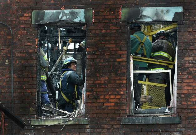 ATF agents search for evidence Tuesday morning, March 10, 2015, in one of the buildings involved in the major fire on Jay Street in Schenectady, N.Y.  (Skip Dickstein/Times Union) Photo: SKIP DICKSTEIN / 00030956A