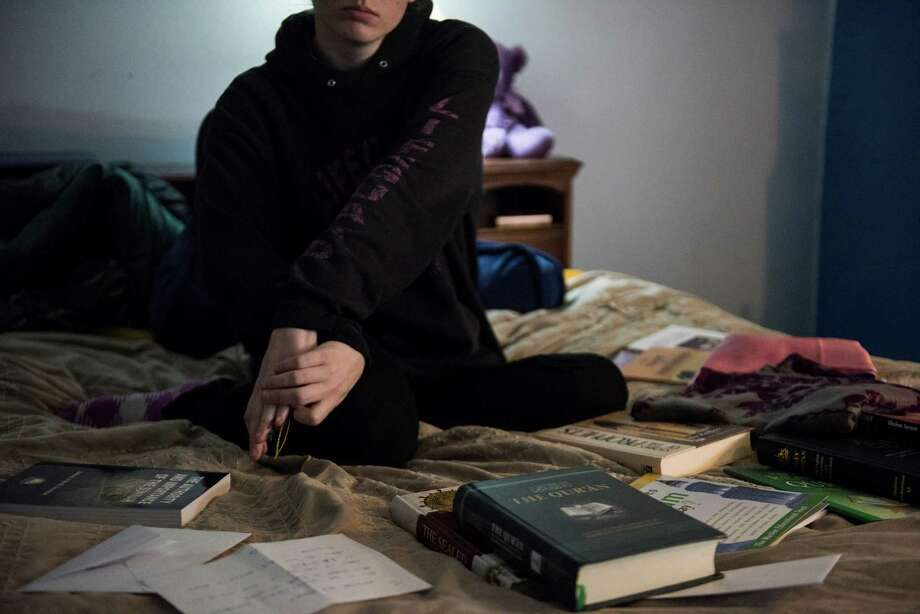 Alex, 23, at home in Washington state on March 8 with books and other gifts from a man who ushered her toward extremist beliefs via months of interaction on social media. The religious texts, prayer rugs, hijabs and chocolates were part of an effort to convert the increasingly adrift young woman to Islam over Twitter. (Andrea Bruce/The New York Times) -- NO SALES; FOR EDITORIAL USE ONLY WITH STORY SLUGGED US-ISLAMIC-RECRUIT BY CALLIMACHI. ALL OTHER USE PROHIBITED. -- Photo: ANDREA BRUCE, STR / NYTNS
