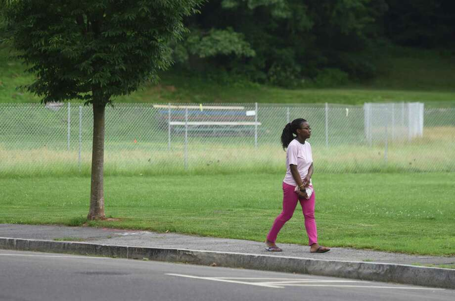 Jessica Osagie, 14, of Byram, walks by the fenced off William Street ball field in the Byram section of Greenwich. A recent test has found levels of arsenic in the soil so high that it must be cleaned up and reported to the state. Photo: Tyler Sizemore / Hearst Connecticut Media / Greenwich Time