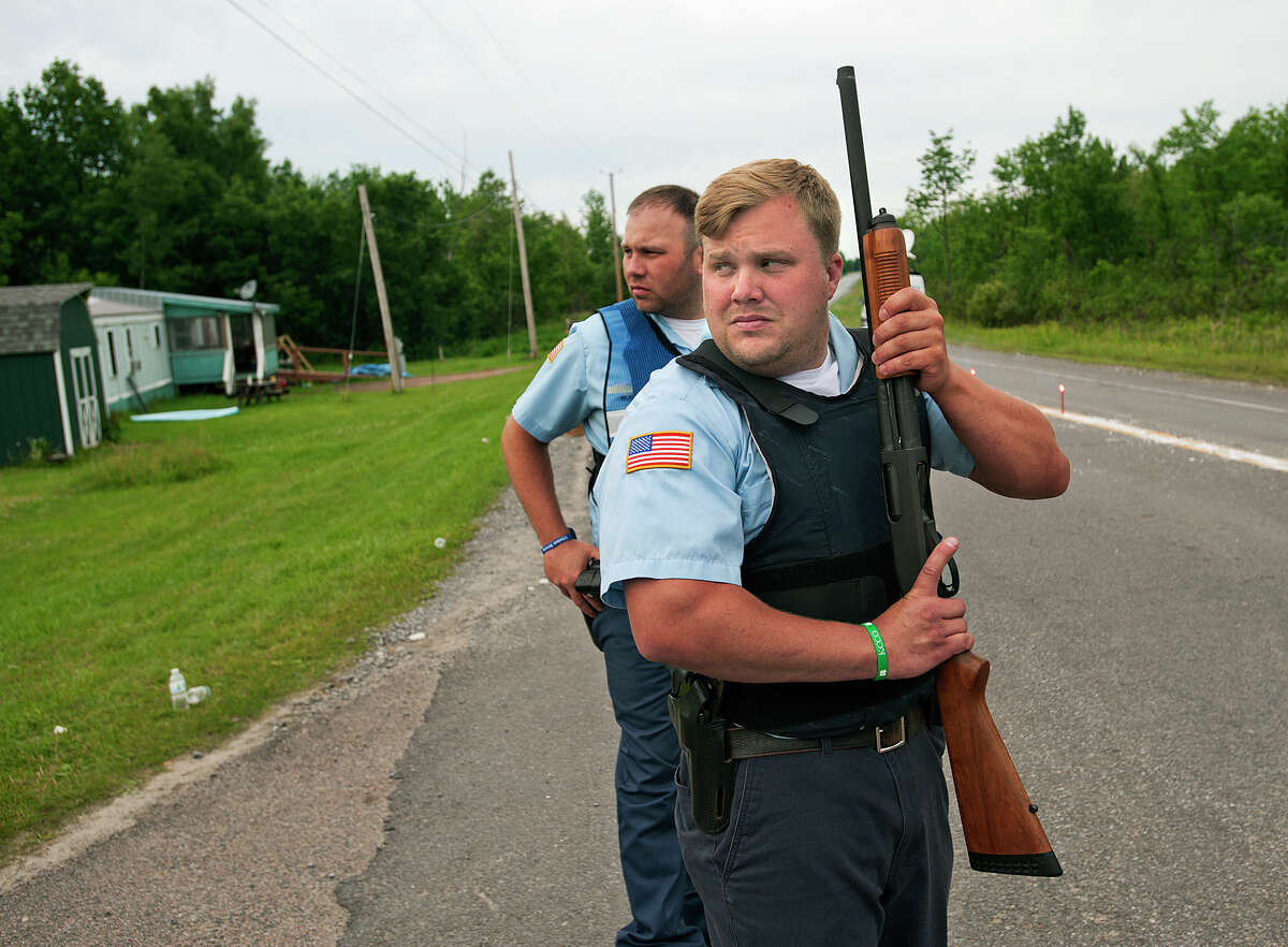 New York State corrections officers stand guard to check vehicles along State Route 30 at the intersection with Travers Rd. in the town of Malone, N.Y. on Saturday, June 27, 2015 as the search for escaped prisoner David Sweat continues. (Jason Hunter/Watertown Daily Times via AP) ORG XMIT: NYWAT108