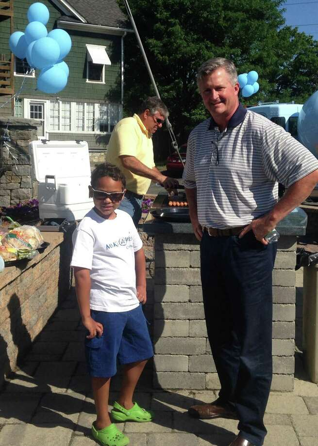 """Make-A-Wish recipient, Connor Armstrong, 7, of Stamford with Sam Gault, president of Gault Energy & Stone, during a barbecue held in Connor's honor at the company's Westport headquarters. The event was to celebrate the company's """"Dollars for Dreams"""" fundraising campaign, which raised  $10,000 to send Connor and his family to Atlantis Resorts in the Bahamas. Gault Energy & Stone Vice President Jim Donaher mans the grill in the background. Photo: Contributed Photo / Contributed Photo / westport news"""