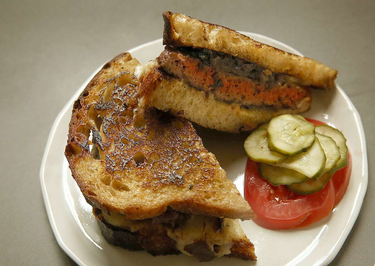 Owner/chef Chris Kronner butters a piece of bread while showing how to make a patty melt at home in Oakland, Calif., on Wednesday, June 24, 2015.