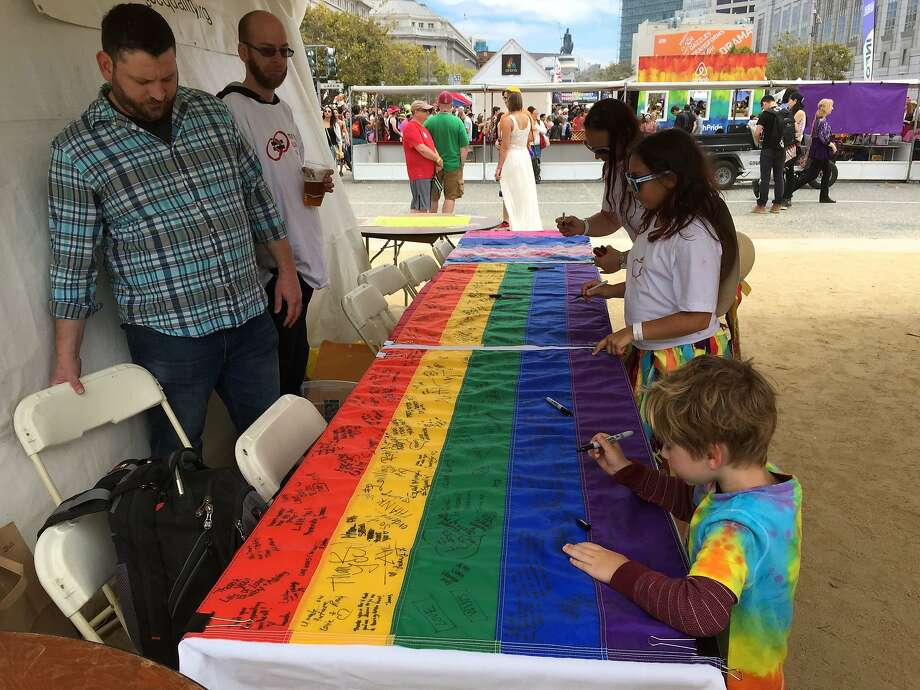 Ronan Hart, 4, front, signs a rainbow flag being sent to the U.S. Supreme Court justices who ruled in favor of same-sex marriage rights. Ronan signed the flag at San Francisco's Pride Parade on June 29, 2015. Photo: Evan Sernoffsky