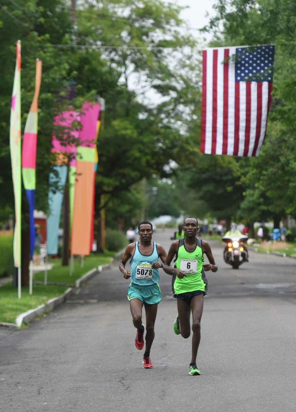 Ethiopia's Gosa Girma Tefera, left, battles Kenya's Josphat Kiptanui Too in the final miles of the Faxon Law Group Fairfield Half Marathon at Jennings Beach in Fairfield, Conn. Sunday, June 28, 2015. Gosa Girma Tefera, of Ethiopia, was the first place overall finisher with a time of 1:04:05 and Josphat Kiptanui Too finished in second with a time of 1:04:09. Etaferahu Temesgen, of Ethiopia, was the first female finisher with a time of 1:14:09.