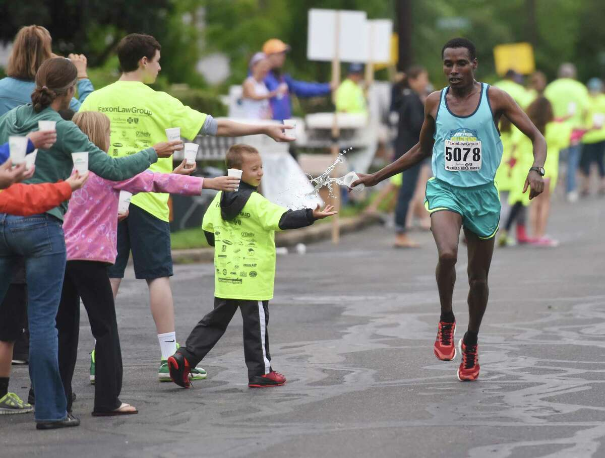 Gosa Girma Tefera, of Ethiopia, grabs a cup of water coming down the final stretch of the Faxon Law Group Fairfield Half Marathon at Jennings Beach in Fairfield, Conn. Sunday, June 28, 2015. Gosa Girma Tefera, of Ethiopia, was the first place overall finisher with a time of 1:04:05 and Etaferahu Temesgen, of Ethiopia, was the first female finisher with a time of 1:14:09.