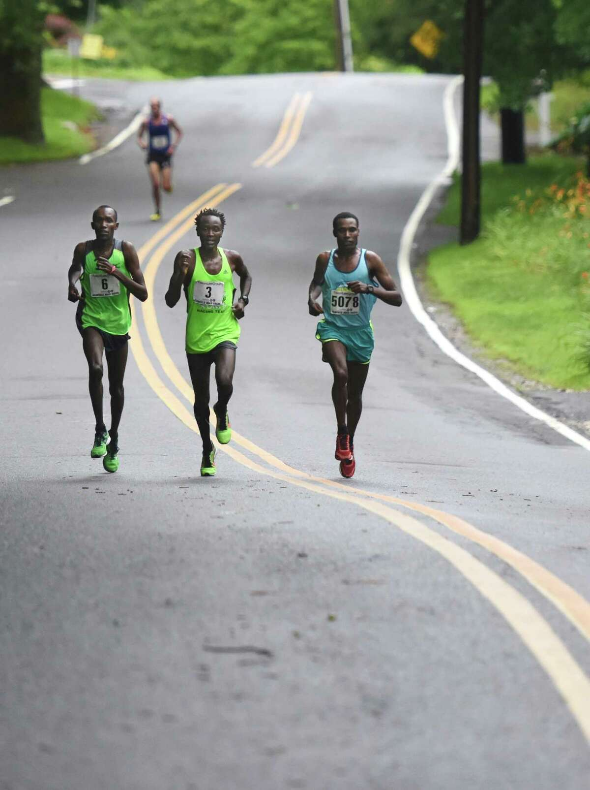 Second-place finisher Kenya's Josphat Kiptanui Too, left, third-place finisher Kenya's Eliud Ngetich, center, and race winner Ethiopia's Gosa Girma Tefera battle it out midway through the Faxon Law Group Fairfield Half Marathon at Jennings Beach in Fairfield, Conn. Sunday, June 28, 2015. Gosa Girma Tefera, of Ethiopia, was the first place overall finisher with a time of 1:04:05 and Etaferahu Temesgen, of Ethiopia, was the first female finisher with a time of 1:14:09.