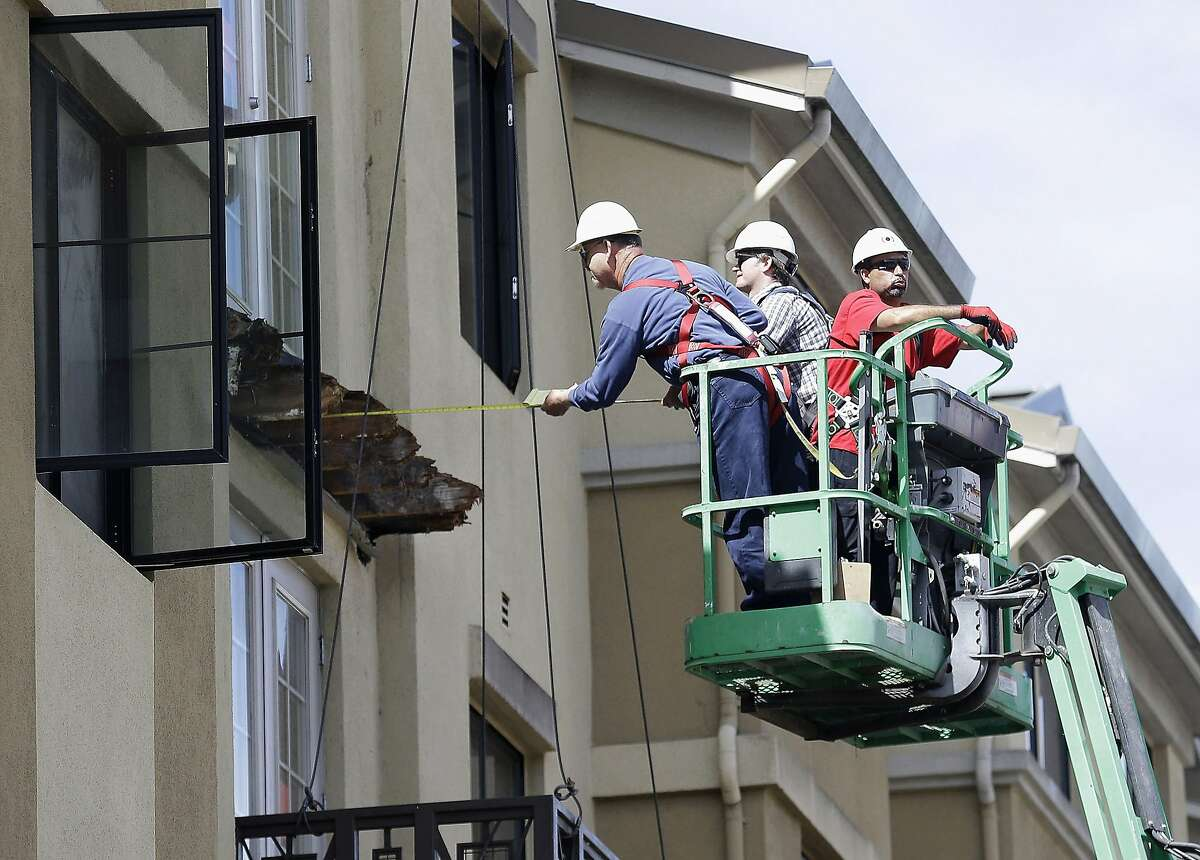 FILE- In this Wednesday, June 17, 2015 file photo, a worker measures near the remaining wood from an apartment building balcony that collapsed in Berkeley, Calif. The balcony broke loose from the building during a 21st birthday party early Tuesday, June 16, 2015, killing several people and seriously injuring others. Prosecutors in the San Francisco Bay Area say they will lead a criminal investigation into the Berkeley balcony collapse that killed six college students. The development comes after building inspectors said the fifth-floor balcony that snapped off an apartment building was supported by wooden beams badly rotted by exposure to moisture.