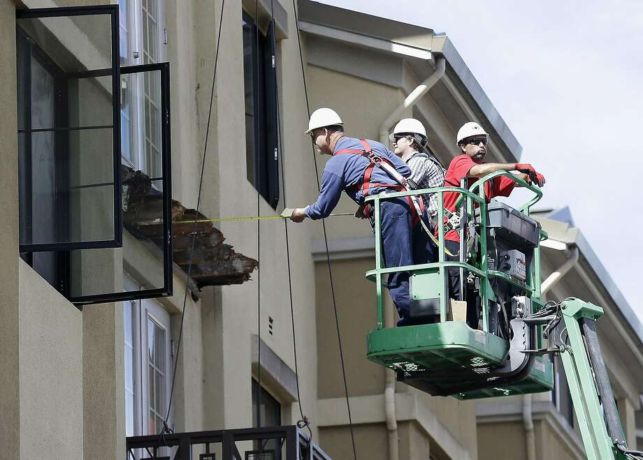 FILE- In this Wednesday, June 17, 2015 file photo, a worker measures near the remaining wood from an apartment building balcony that collapsed in Berkeley, Calif. The balcony broke loose from the building during a 21st birthday party early Tuesday, June 16, 2015, killing several people and seriously injuring others. Prosecutors in the San Francisco Bay Area say they will lead a criminal investigation into the Berkeley balcony collapse that killed six college students. The development comes after building inspectors said the fifth-floor balcony that snapped off an apartment building was supported by wooden beams badly rotted by exposure to moisture.  Photo: Jeff Chiu, Associated Press