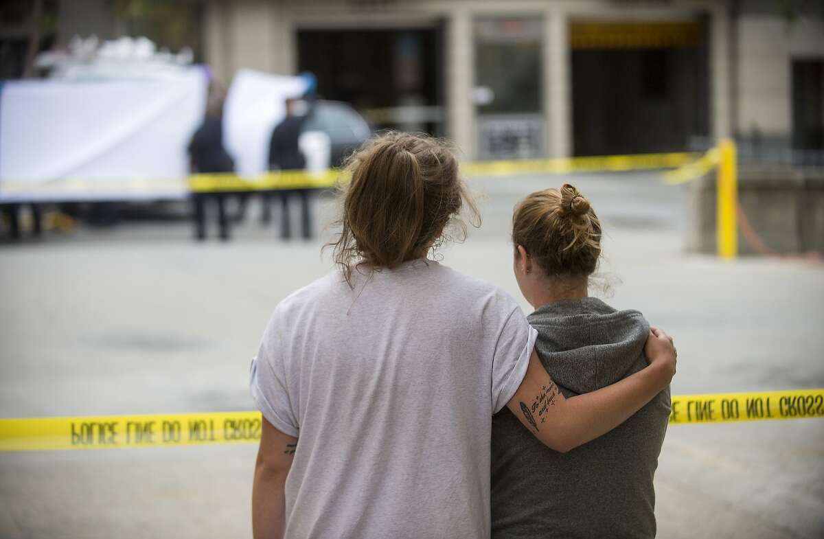 FILE - In this June 16, 2015, file photo, two women embrace while watching sheriff's deputies move the body of a person who died when a fourth floor balcony collapsed in Berkeley, Calif. The two said they knew the victims of the collapse. Prosecutors in the San Francisco Bay Area say they will lead a criminal investigation into the Berkeley balcony collapse that killed six college students. The development comes after building inspectors said the fifth-floor balcony that snapped off an apartment building was supported by wooden beams badly rotted by exposure to moisture.