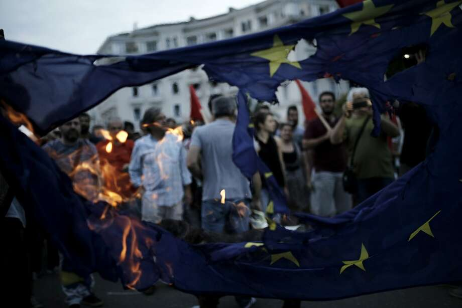 Protesters burn a European Union (EU) flag during an anti-austerity demonstration in Thessaloniki, Greece, on Sunday, June 28, 2015. Greece moved to avert the collapse of its financial system, shutting its lenders as of Monday, a measure that will deepen the recession and risk driving the nation toward an exit from the euro. Photographer: Konstantinos Tsakalidis/Bloomberg Photo: Konstantinos Tsakalidis, Bloomberg