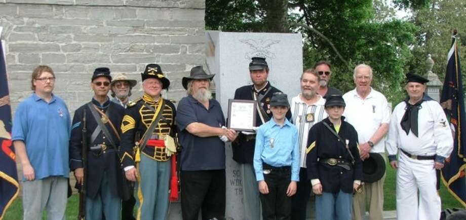 SCHOHARIE — At the Decoration Day Commemoration on May 30, at the Old Stone Fort, Richard Sherman of the Corporal James Tanner Camp #134, Sons of Union Veterans of the Civil War received a commendation from Camp Commander Peter Lindemann.  Sherman was instrumental in the erecting of the Schoharie County Civil War Monument at the Old Stone Fort, which was dedicated on May 30, 2011.  Anyone who would like to buy a commemorative paver to be placed on the apron of the monument may contact Richard Sherman at rsherman4@nycap.rr.com.  Sherman is now in the early planning stages for erecting a War of 1812 monument as well as a monument to honor the women of Schoharie County. He is currently looking for others who are interested in supporting and/or working on these projects. Pictured (left to right) are Jeremi Sherman, Richard Christman, Vern Hall, Museum Director Carle Kopecky, Richard Sherman, Peter Lindemann, Andrew Wheat, Mel Bostwick, Gerry Wright, Christopher Bostwick, Art Warner, and Vern Wagner.