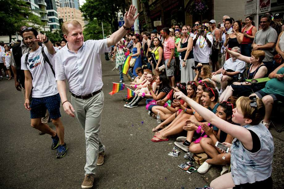 Mayor Ed Murray, center, and spouse Michael Shiosaki, left, greet onlookers during Seattle's 41st annual Pride Parade last June.  Photo: JORDAN STEAD, SEATTLEPI.COM / SEATTLEPI.COM
