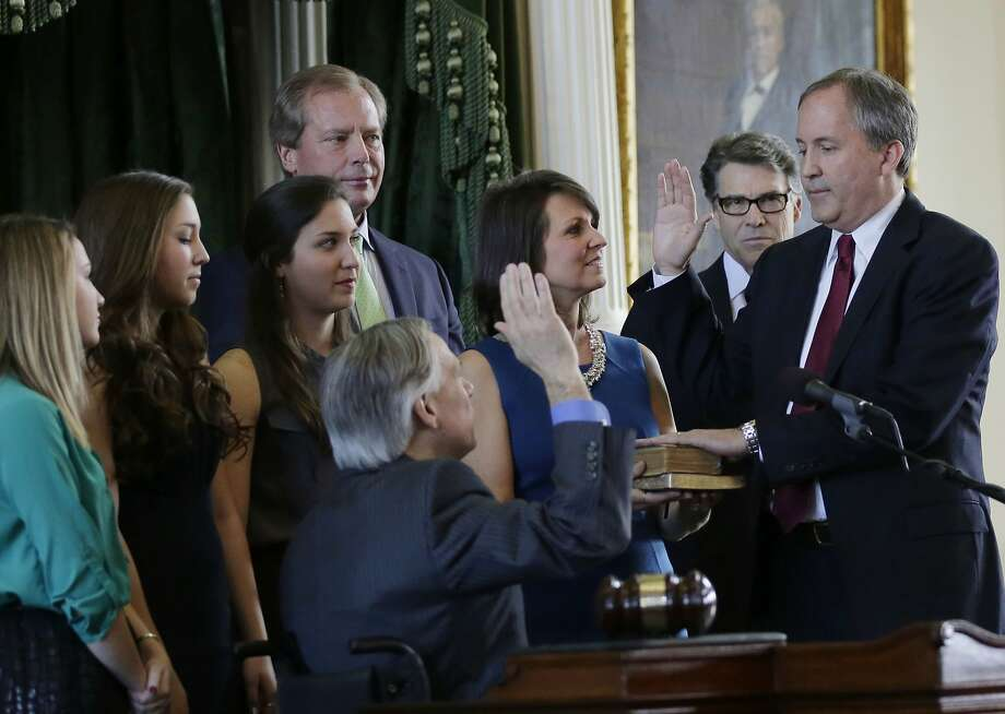 Ken Paxton, right, is sworn in as Texas attorney general by Gov.-elect Greg Abbott, center, Monday, Jan. 5, 2015, in Austin, Texas. Paxton is joined by his family and Gov. Rick Perry, second from right. (AP Photo/Eric Gay) Photo: Eric Gay, Associated Press