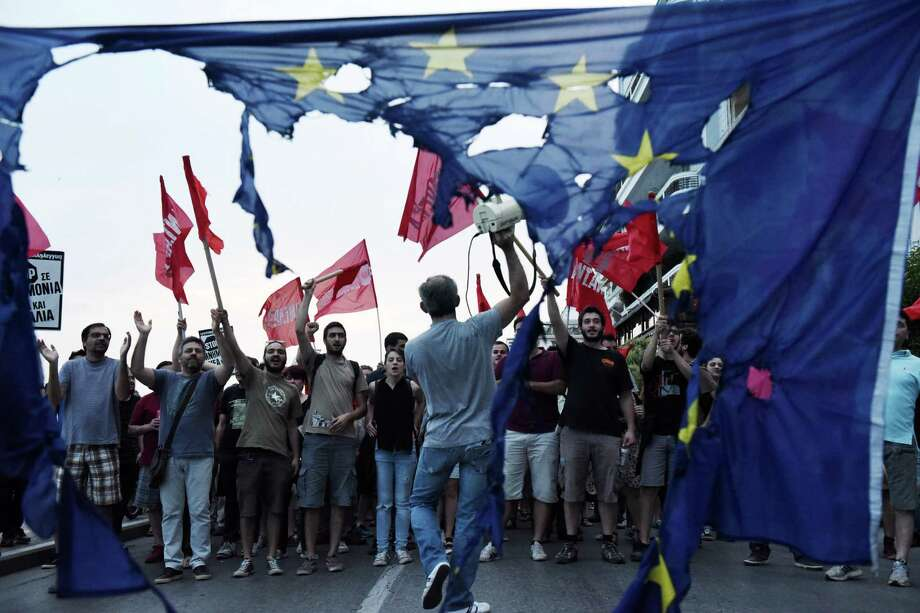 Members of left wing parties shout slogans behind a burning European Union flag during an anti-EU protest in the northern Greek port city of Thessaloniki, Sunday, June 28, 2015.  Greek Prime Minister Alexis Tsipras says the Bank of Greece has recommended that banks remain closed and restrictions be imposed on transactions, after the European Central Bank didn't increase the amount of emergency liquidity the lenders can access from the central bank. (AP Photo/Giannis Papanikos) Photo: Giannis Papanikos, STR / AP