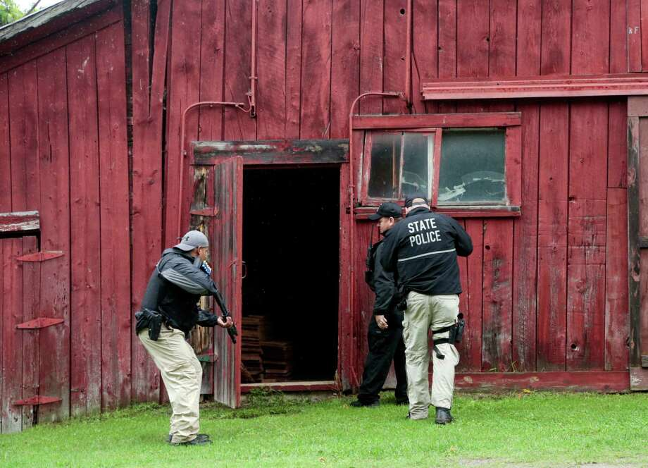 New York state police officers enter a barn Sunday during a search for convicted murderer David Sweat, who eventually was found walking along a road near the Canadian border. Photo: Mike Groll, STF / AP