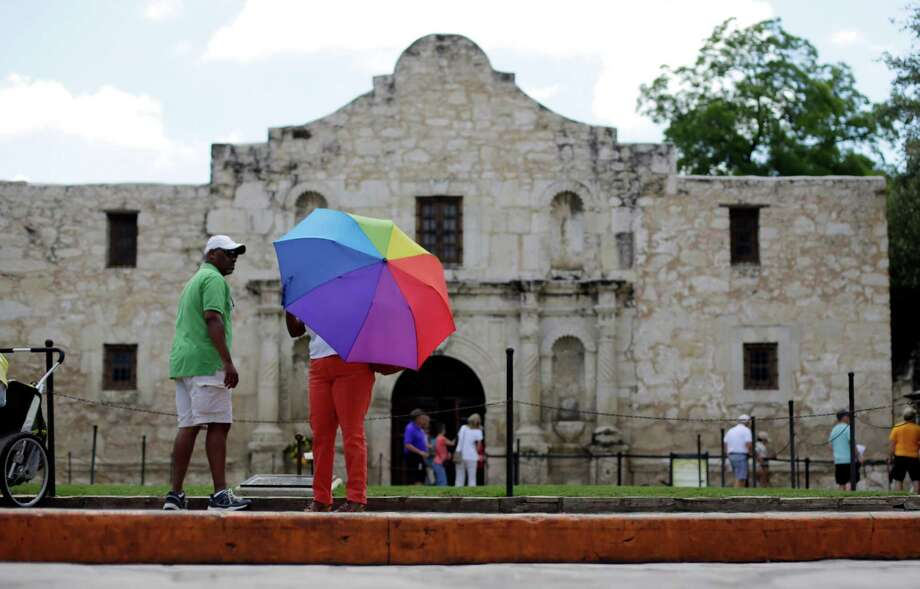 A visitor uses an umbrella to shield the sun during a visit to the Alamo, Monday, June 15, 2015, in San Antonio. The Alamo,  site of the Battle of the Alamo in the Texan War of Independence from Mexico, is one of the most visited historical sites in Texas. (AP Photo/Eric Gay) Photo: Eric Gay, STF / AP