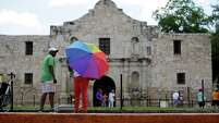 A visitor uses an umbrella to shield the sun during a visit to the Alamo, Monday, June 15, 2015, in San Antonio. The Alamo,  site of the Battle of the Alamo in the Texan War of Independence from Mexico, is one of the most visited historical sites in Texas. (AP Photo/Eric Gay)