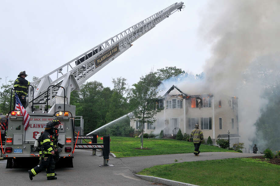 Firefighters work to extinguish flames after a small plane crashed into a house in Plainville, Mass., Sunday, June 28, 2015. Jim Peters of the Federal Aviation Administration says the Beechcraft plane crashed into the house at about 5:45 p.m. Sunday. It had taken off from Lancaster Airport in Pennsylvania and was en route to an airport in Norwood, Mass. (Mark Stockwell/The Sun Chronicle via AP) Photo: Mark Stockwell, MBR / The Sun Chronicle