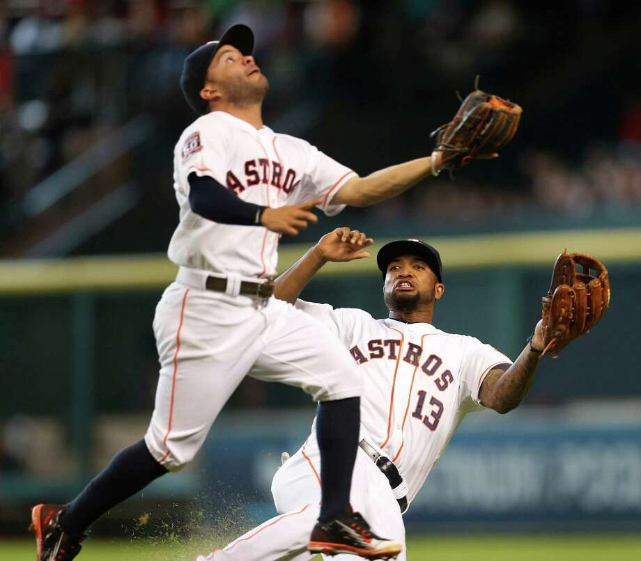 Astros second baseman Jose Altuve  finds himself with the upper hand toward catching Alex Rodriguez's popup while avoiding right fielder Domingo Santana. Photo: Karen Warren, Staff / © 2015 Houston Chronicle