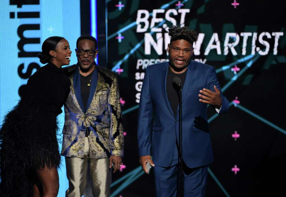 Kelly Rowland, from left, and Charlie Wilson present the award for best new artist to Anthony Anderson accepting on behalf of Sam Smith at the BET Awards at the Microsoft Theater on Sunday, June 28, 2015, in Los Angeles. (Photo by Chris Pizzello/Invision/AP) Photo: Chris Pizzello, INVL / Invision