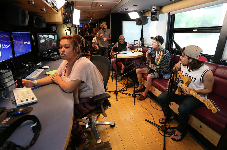 """BCFS San Antonio Transitional Center student Alexis Rabago, 18, helps out with remote cameras as members of """"Never Shout Never"""" prepare to record in the John Lennon Educational Bus during the Vans Warped Tour at the AT&T Center, Sunday, June 28, 2015. The bus is a non-profit set up to teach students sound engineering and multimedia productions. Three students from the center helped record the band's song """"Piggy Bank."""" Photo: JERRY LARA /San Antonio Express-News / © 2015 San Antonio Express-News"""