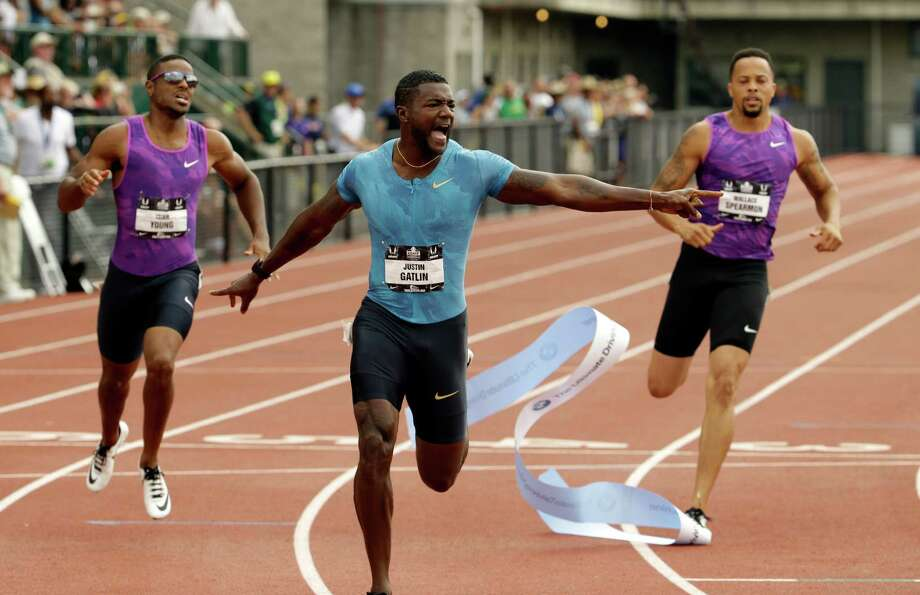 Justin Gatlin, center, points out his winning time of 19.57 in the 200 meters. Photo: Don Ryan, STF / AP