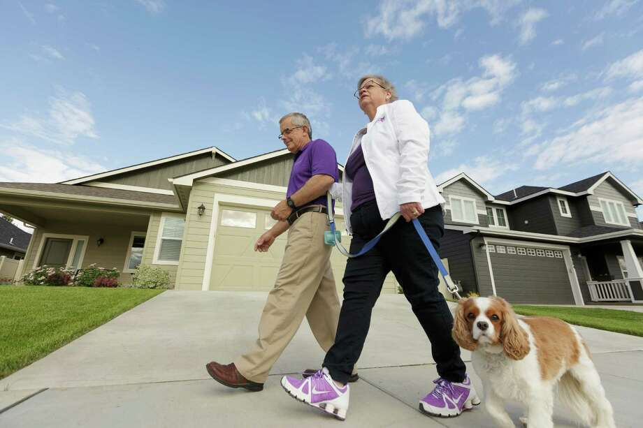 Amy Shives, right, and her husband George walk their cavalier King Charles spaniel Chester in their neighborhood, Wednesday, June 3, 2015, in Spokane, Wash. Amy Shives was diagnosed with early onset Alzheimer's disease in 2011 and has since been involved with the Alzheimer's Association. Nearly two-thirds of Americans with Alzheimer's disease are women, and now some scientists are questioning the long-held assumption that it's just because women tend to live longer than men. (AP Photo/Young Kwak) ORG XMIT: WX202 Photo: Young Kwak / FR159675 AP