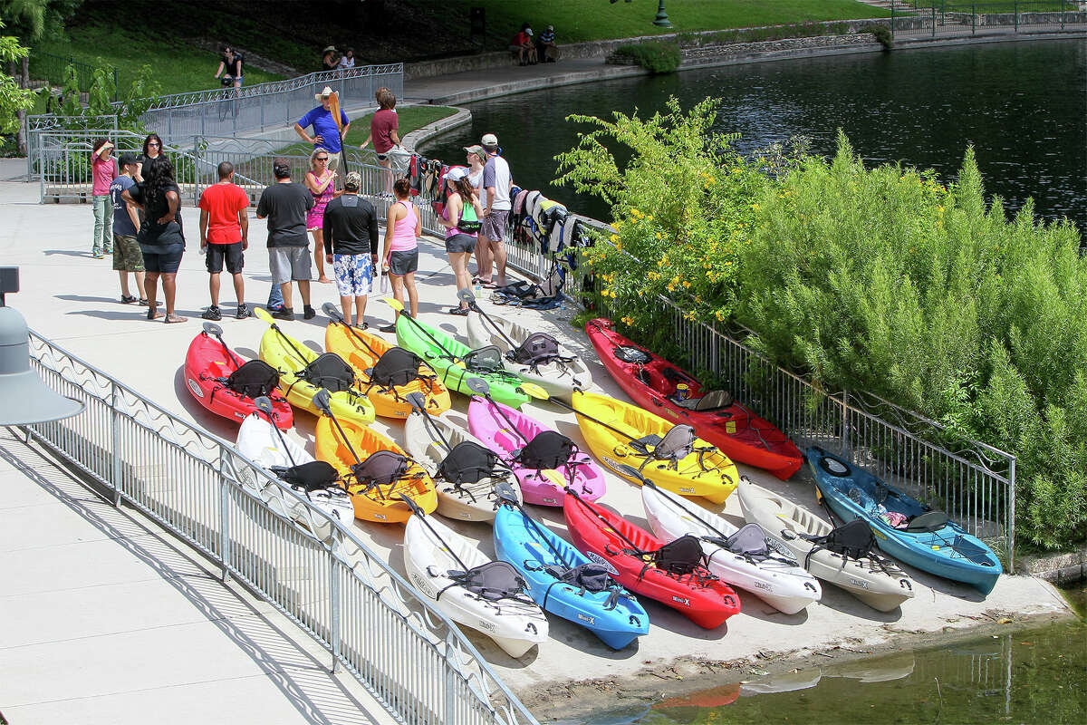 Stacey Banta, a certified kayak instructor with Texas Pack and Paddle (holding paddle), gives instructions for a tour on the San Antonio River. She leads beginners in the King William area.