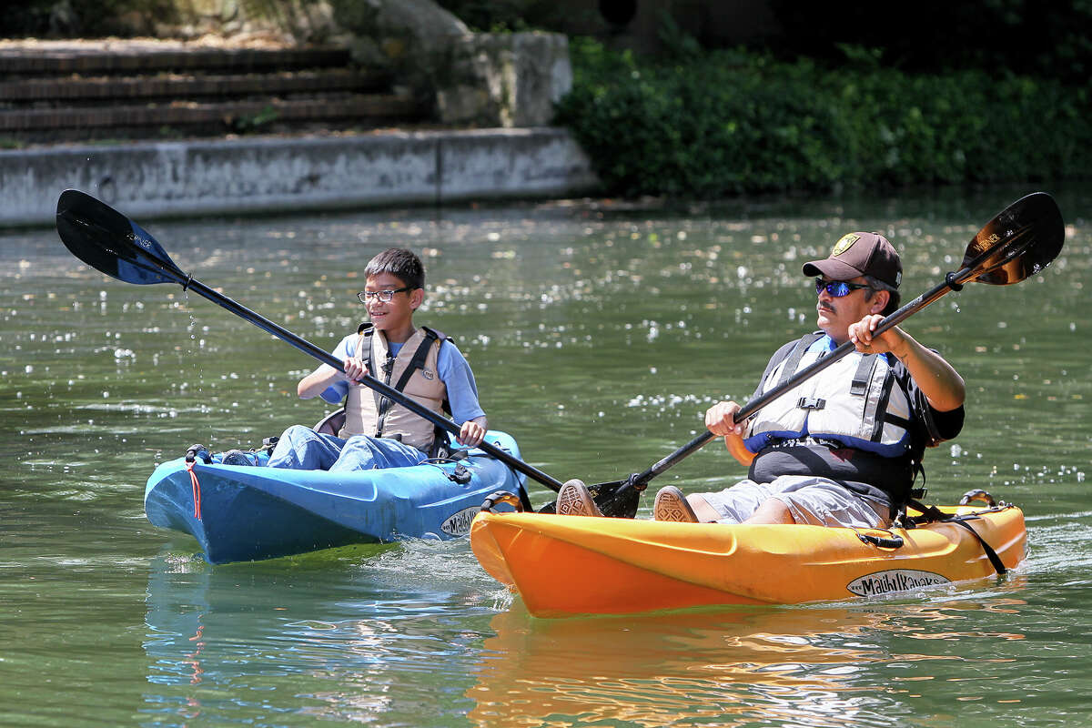 Miguel Alvarado and son Kevin, 12, paddle along the river during a guided kayak tour.