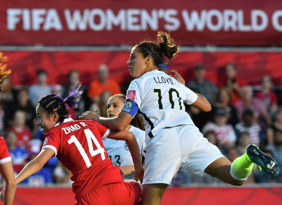 US player Carli Lloyd (R) looks on as she scores a goal during a 2015 FIFA Women's World Cup quarterfinal match between the US and China at Lansdowne Stadium in Ottawa, Ontario on June 26, 2015.    AFP PHOTO/NICHOLAS KAMMNICHOLAS KAMM/AFP/Getty Images ORG XMIT: 528452931 Photo: NICHOLAS KAMM / AFP