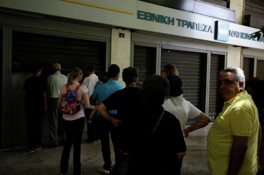 People wait to use ATMs of a bank in central Athens, Sunday, June 28, 2015. Greece is anxiously awaiting a decision by the European Central Bank on whether to increase the emergency liquidity assistance banks can draw on from the country's central bank. (AP Photo/Thanassis Stavrakis) ORG XMIT: ATH117 Photo: Thanassis Stavrakis / AP