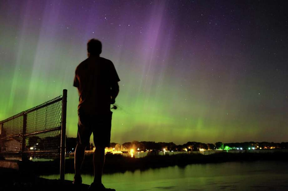 Wade Kitner looks at the northern lights as he fishes in Ventura, Iowa, on Tuesday, June 23, 2015. Federal forecasters said the Northern Lights may be able to be seen Tuesday night as far south as Iowa or Pennsylvania because of a severe solar storm that hit the Earth on Monday and pushes auroras to places where more people can possibly see them. Photo: Arian Schuessler, AP / Globe Gazette