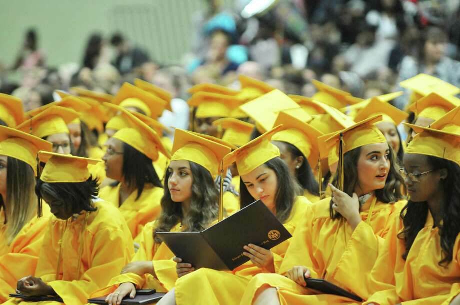 Graduates watch as their fellow graduates receive their diplomas at the Troy High School graduation at Hudson Valley Community College, on Sunday, June 28, 2015, in Troy, N.Y.  (Paul Buckowski / Times Union) Photo: PAUL BUCKOWSKI / 00032185A