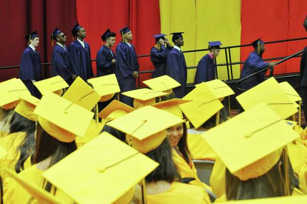 A group of boys make their way onto the stage to receive their diploma as girls look on at the Troy High School graduation at Hudson Valley Community College, on Sunday, June 28, 2015, in Troy, N.Y.  (Paul Buckowski / Times Union) Photo: PAUL BUCKOWSKI / 00032185A