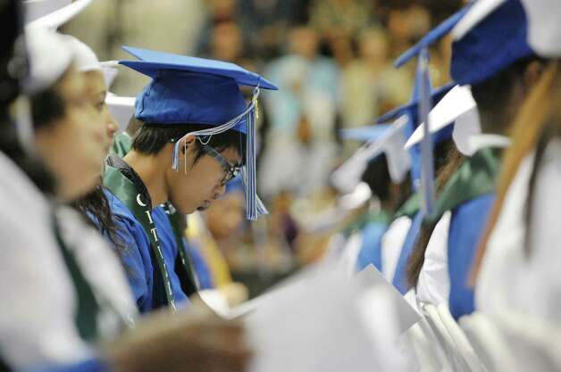 A graduate looks over the program during the Albany High School graduation at the SEFCU Arena on the campus of the University at Albany, on Sunday, June 28, 2015, in Albany, N.Y.  (Paul Buckowski / Times Union) Photo: PAUL BUCKOWSKI / 00032184A