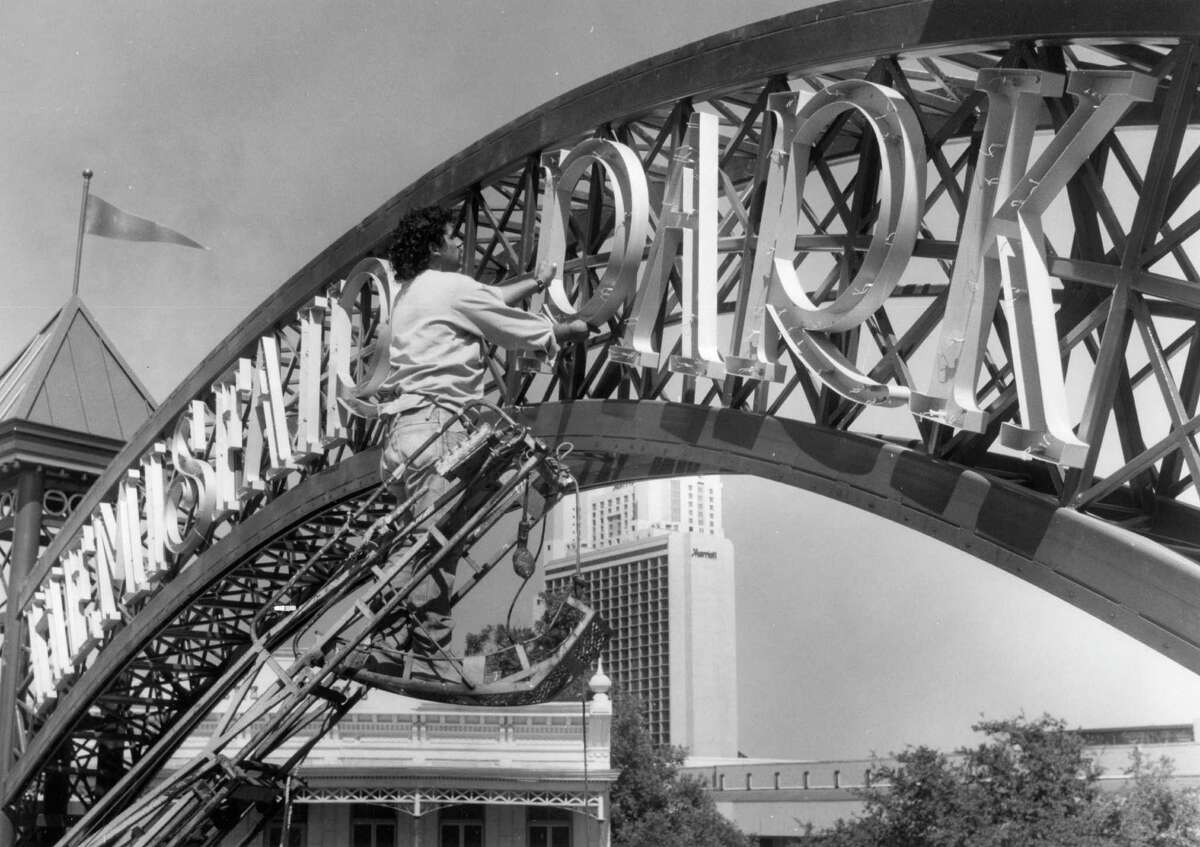 Jesse Lopez of the AAA Signs of San Antonio places the large metal letters on the entrance way to HemisFair Park, 1989.