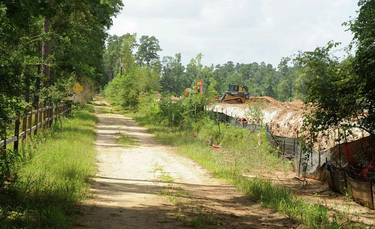 Construction on an apartment complex next to W.G. Jones State Forest, on left, at F.M. 1488 is underway with ground work being done. Photograph by David Hopper.