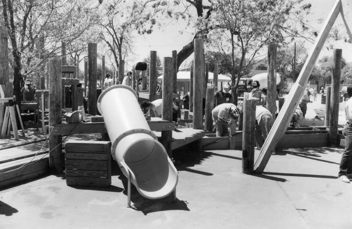 Volunteers assemble the wooden play structure at HemisFair Park, 1989.