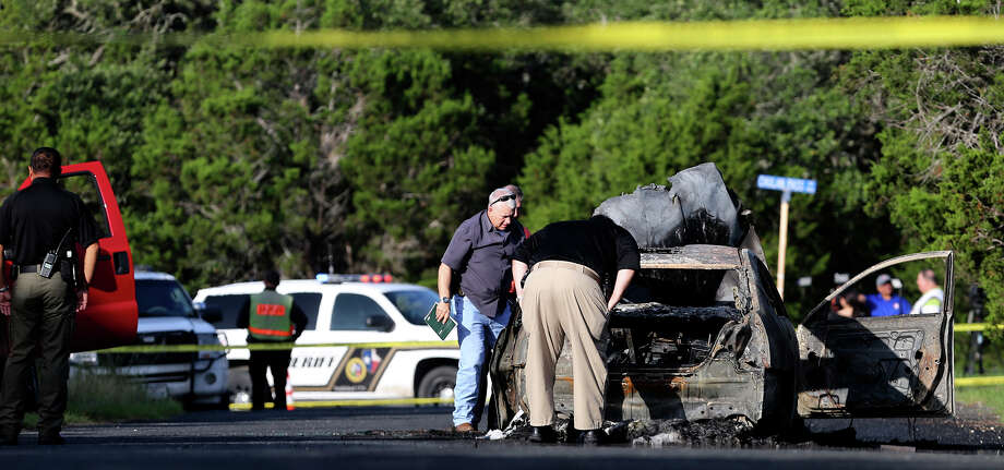 Officials examine a burned car Monday June 29, 2015 in which a body was found in the trunk near Chulan Pass and Monarch Pass in northwest Bexar County. The Bexar County Sheriff's Office said it received a call about the burning car about 5:30 a.m.. The sex of the burned body has not yet been determined. Photo: John Davenport, San Antonio Express-News / ©San Antonio Express-News/John Davenport