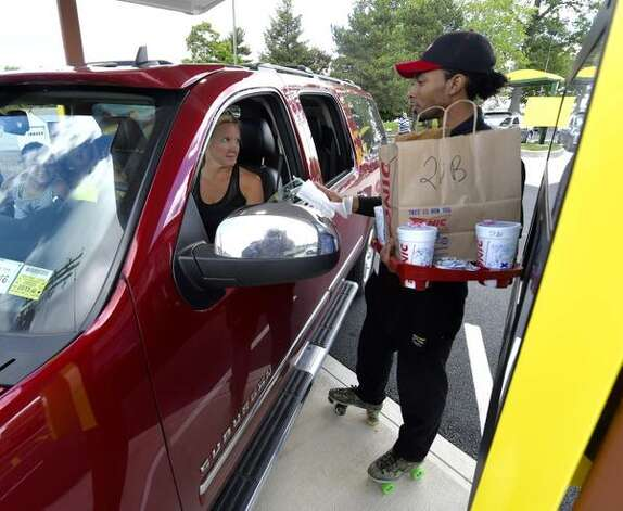 Carhop Sean Little delivers Sonic goodies to McKenzie Venetz and her kids at Sonic in Latham, NY, during the restaurant's soft opening day. (Skip Dickstein/Times Union)