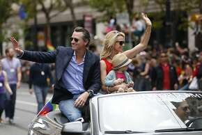 California Lt. Gov. Gavin Newsom, left, and his wife Jennifer holding daughter Brooklynn, wave to spectators during the 45th annual San Francisco Gay Pride parade Sunday, June 28, 2015, in San Francisco. A large turnout was expected for gay pride parades across the U.S. following the landmark Supreme Court ruling that said gay couples can marry anywhere in the country. (AP Photo/ Tony Avelar)