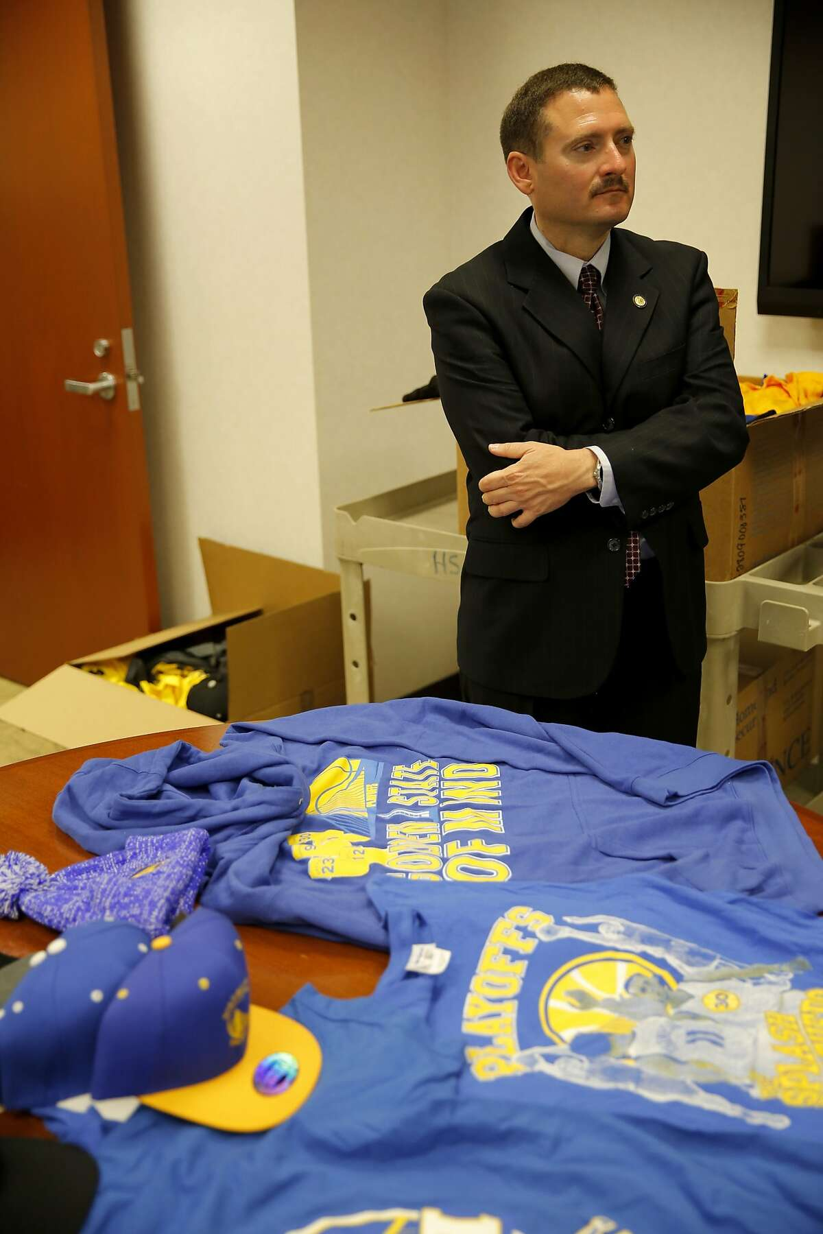 Tatum King, Acting Special Agent in Charge for Homeland Security Investigations in San Francisco, stands in front of seized Golden State Warriors shirts and hats in a conference room of the U.S. Immigration and Customs Enforcement's Homeland Security Investigations department in San Francisco, California, on Monday, June 29, 2015. The Department said it seized nearly half a million dollars in counterfeit gear.
