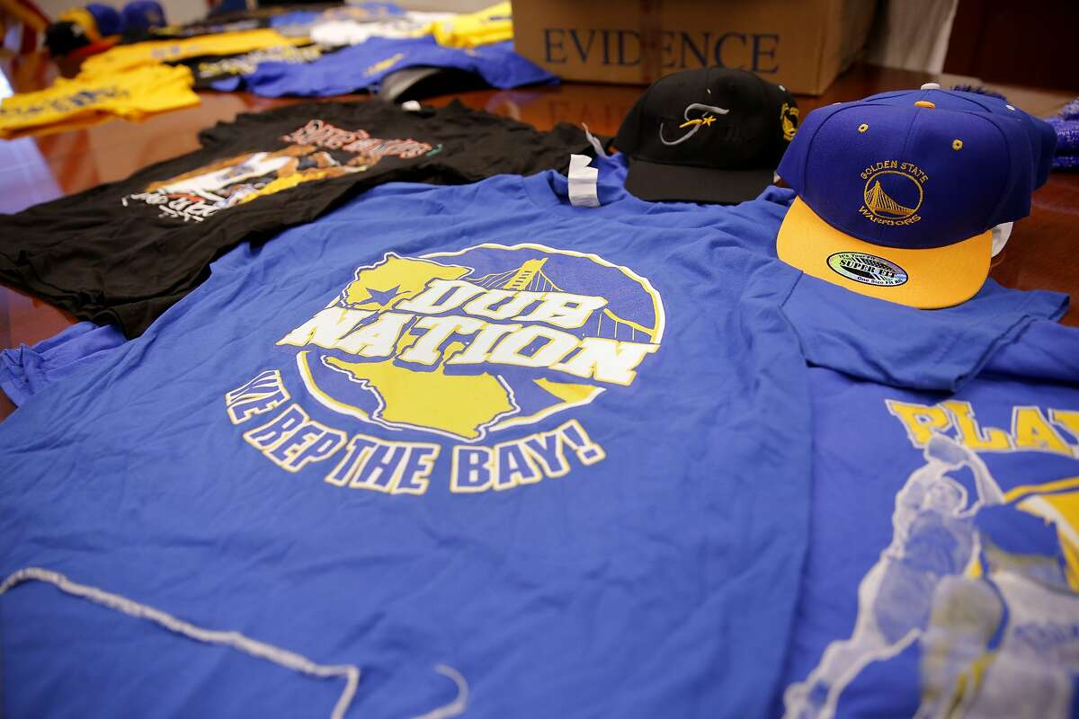 Seized Golden State Warriors shirts and hats lie on a table in a conference room of the U.S. Immigration and Customs Enforcement's Homeland Security Investigations department in San Francisco, California, on Monday, June 29, 2015. The Department said it seized nearly half a million dollars in counterfeit gear.