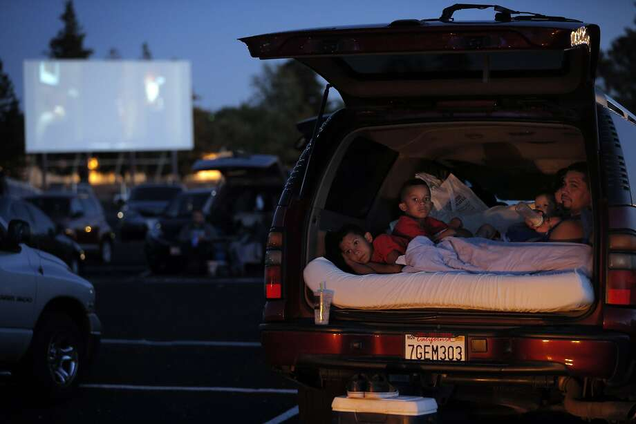 "The Chayrez family of Oakley watches ""Inside Out"" as Jurrasic World plays on the screen behind them at the West Wind Solano 2 drive-in theater in Concord, Calif., on Sunday, June 28, 2015. Drive-in theaters are a special breed of theater where patrons set up tables, deck chairs, even couches and watch the movie while seated outside, or from the back of a lifted hatch on an SUV. The sound is on FM radio frequencies so those old boxes attached to the window no longer exist. Photo: Carlos Avila Gonzalez, The Chronicle"