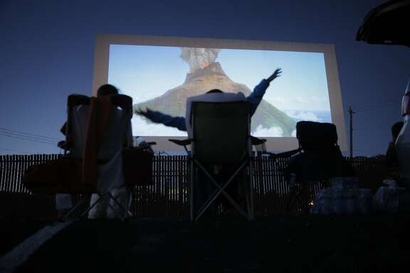 """Jasmine Guerrero, 7, reacts as she watches the Pixar short film """"Lava"""" at the West Wind Solano 2 drive-in theater in Concord, Calif., on Sunday, June 28, 2015. Drive-in theaters are a special breed of theater where patrons set up tables, deck chairs, even couches and watch the movie while seated outside, or from the back of a lifted hatch on an SUV. The sound is on FM radio frequencies so those old boxes attached to the window no longer exist."""